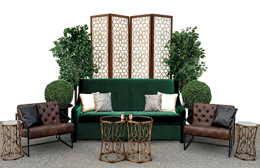 Seating group with green sofa, brown leather chairs, and gold coffee table and end tables